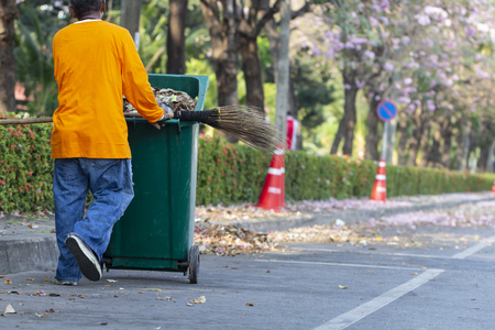 Asian man worker cleaning the road with green trash bin background on daytime.