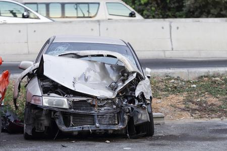 Die Vorderseite des silbernen Autos wird auf der Straße durch einen Unfall beschädigt