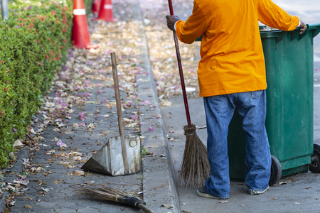Asian man worker cleaning the road with green bin on daytime.