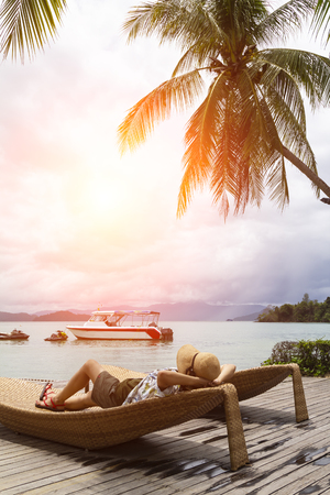 Summer beach vacation concept, Asia woman with hat relaxing and on chair beach with speed boat in back at Koh Payam, Ranong, Thailand Stock Photo