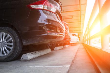 Closeup coches negros estacionados en el edificio de estacionamiento interior con rieles de acero, el concepto de coche de seguridad.