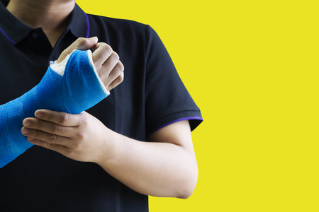 Close up man holding hand with blue bandage as arm injury concept. Isolated on yellow background with copy space. Stock fotó