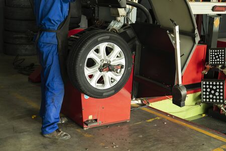 Man worker employee with wheel balancing machine for car tire repair service.