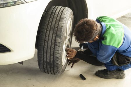 Worker working on car wheel repair at automobile repair service station. Banque d'images