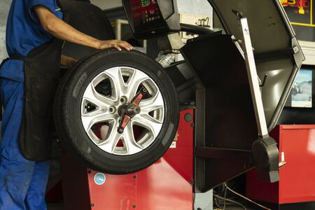 Man worker with Wheel balancing machine for car tire repair service.