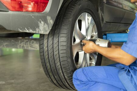 Mechanic changing car wheel with impact wrench at service shop.
