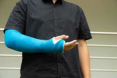 Asian men wear cloth splints on their arms to treat accident injuries. Banque d'images - 130980757