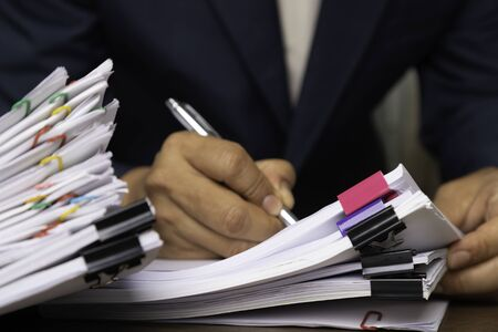 Male office workers holding and writing documents on office desk, Stack of business paper.