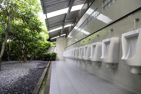 Row of outdoor white urinals men in public toilet.