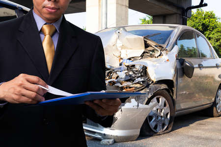 Side view of insurance officer writing on clipboard while insurance agent examining silver car after accident.