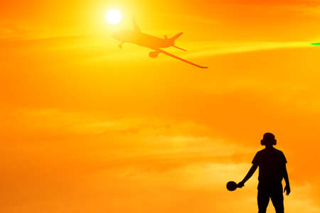 Silhouette of ground staff sending airplane taking off flight with orange sky background and lens flare effect