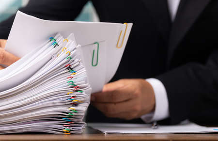Business man or office workers with white shirt holding documents for writing on office desk, Stack of business overload paper. Imagens