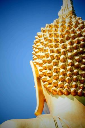 back: Golden buddha head and blue sky.