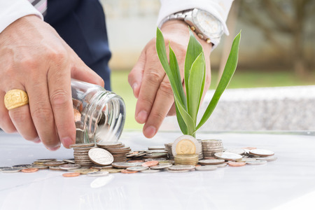 clear bottle: Hand putting mix coins and seed in clear bottle on white background,Business investment growth concept
