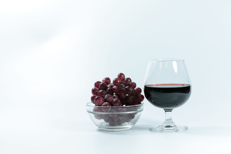 glass of wine and grapes, on white