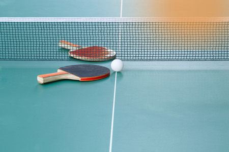 Two table tennis or ping pong rackets and balls on a green table with net