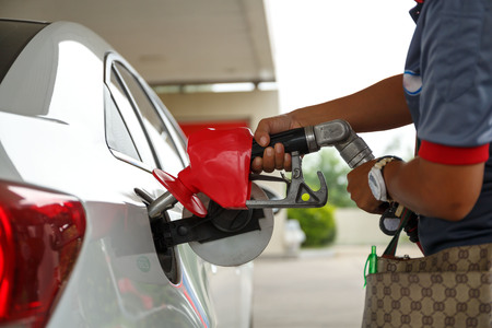 Closeup of woman pumping gasoline fuel in car at gas station. Petrol or gasoline being pumped into a motor vehicle car. Foto de archivo