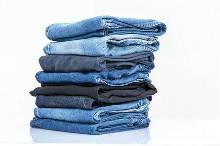 De stapel van jeansbroeken op witte achtergrond