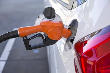 transportation and ownership concept - man pumping gasoline fuel in car at gas station