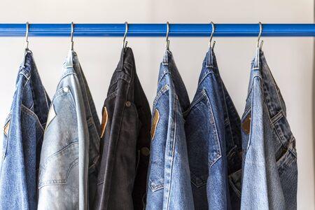 ๋Jeans hanging on a rack. Row of pants denim jeans hanging in closet. concept of buy , sell , shopping and jeans fashion