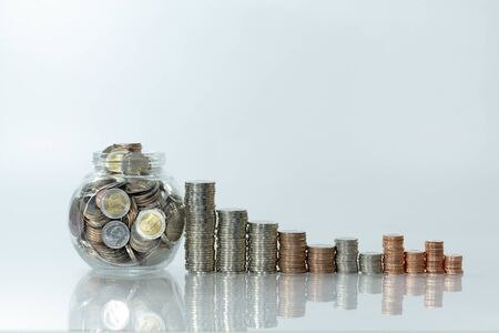 Stack of coin on white table and blur background, selective focus