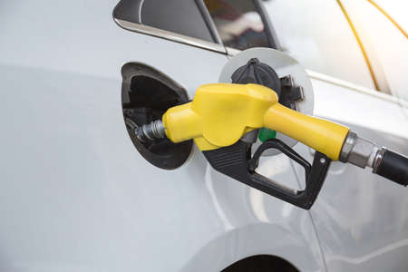 Closeup of woman pumping gasoline fuel in car at gas station. Petrol or gasoline being pumped into a motor vehicle car. Stockfoto