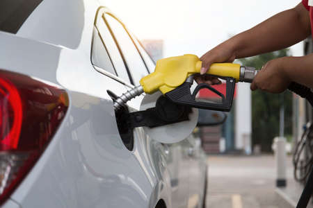 Man pumping gasoline fuel in car at gas station-transportation and ownership concept.