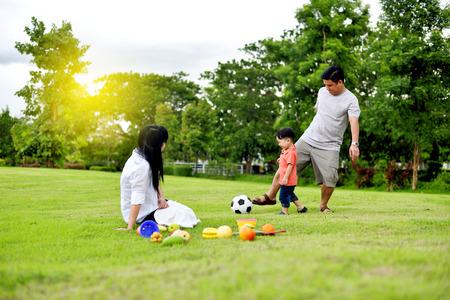 父と母が庭で息子と遊ぶ