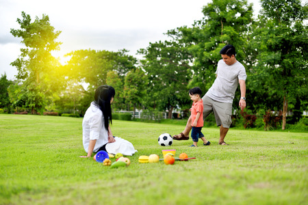 Father and mother play with their son in the garden