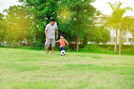 football play: Asian boy play football with his father in the garden Stock Photo