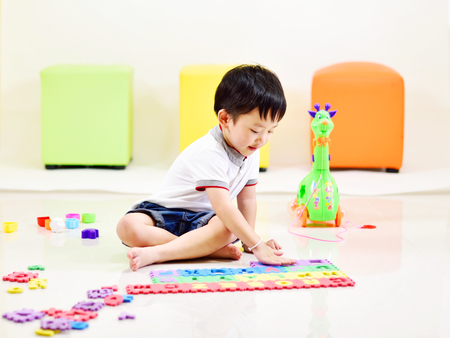 Asian boy playing toys in living room Stockfoto