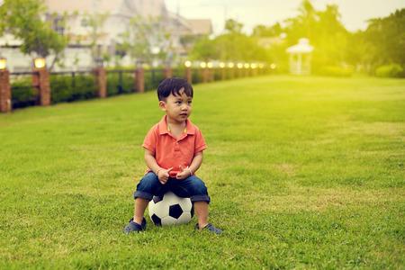 정원에서 축구를하는 아시아 소년