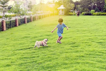 행복 한 아시아 소년 그의 개 정원에서 놀고