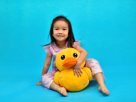 Cute Asian girl playing with doll in living room