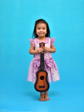 Portrait of Asian girl with ukulele, blue background