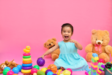 Cute Asian girl playing toys in living room