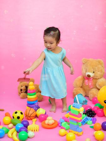 귀여운 아시아 소녀 거실에서 장난감을 연주