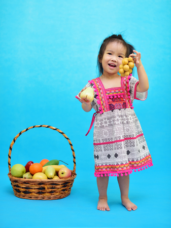 Cute Asian girl with Northern Thai style costume holding fruit in hand