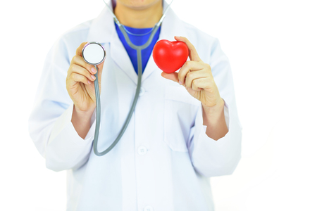 Doctor holding heart in hands with stethoscope Stock Photo