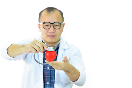 Doctor holding heart in hands with stethoscope, heart care concept Stock Photo