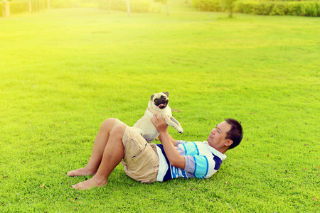 Happy Asian man playing with his dog in garden Stock Photo