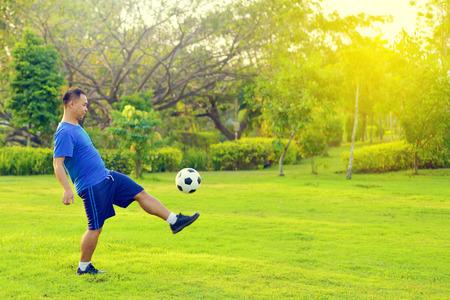 Asian fat man playing football alone in garden