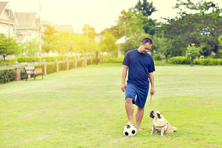 Asian man playing football with brown Pug in garden Stock Photo