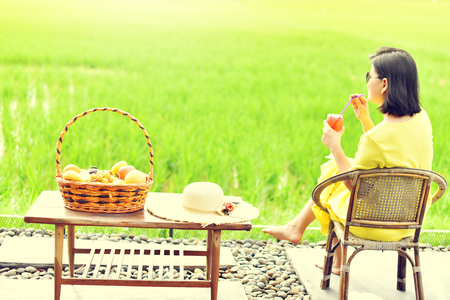 Asian girl with yellow dress sitting on the edge of the rice field Stock Photo