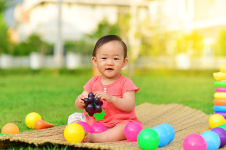 Cute Asian baby playing with toys and smile in playground