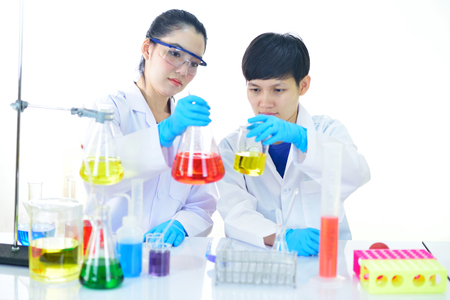 Two Asian female scientists working with chemical in research laboratory