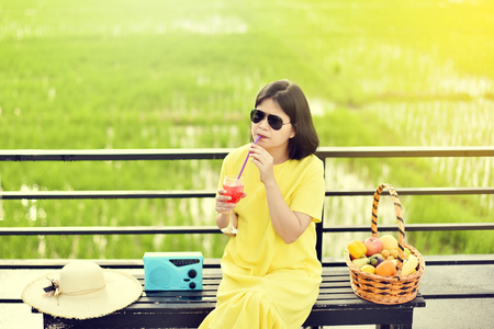 Portrait of Asian girl with yellow dress holding cocktail