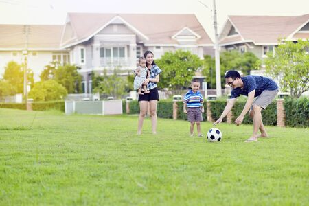 Portrait of Asian family playing football together in garden