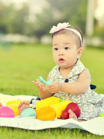 Cute Asian baby girl playing with toys in playground