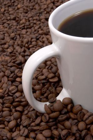 rejuvenate: Cup of coffee in a sea of coffee beans Stock Photo